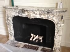 Cheminée ancienne en marbre, de style Régence avec intérieur en fonte