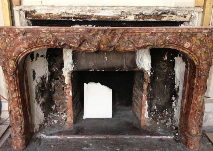 La pose de la cheminée est en cours et on aperçoit bien le foyer préexistant qu'il fallait adapter