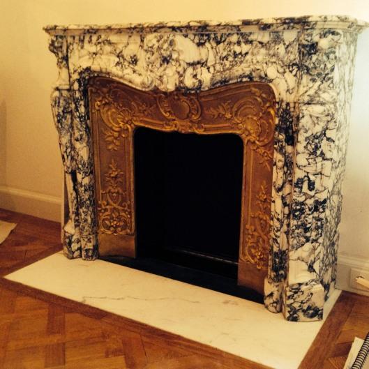 Pose de cheminée de style Louis XV en marbre.