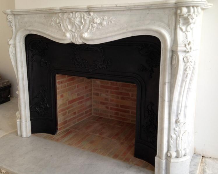 Installation d'une belle cheminée de style Louis XV en marbre de Carrare avec rétrécissement en fonte