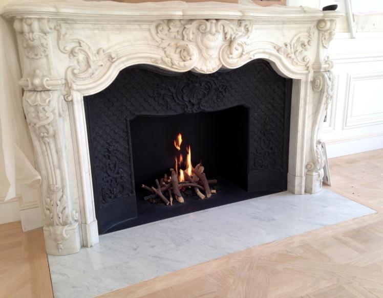 Une superbe cheminée de style Louis XV en marbre avec foyer à l'éthanol.