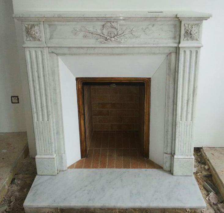 Pose d'une cheminée de style Louis XVI en marbre de Carrare avec rétrécissement en faïence.