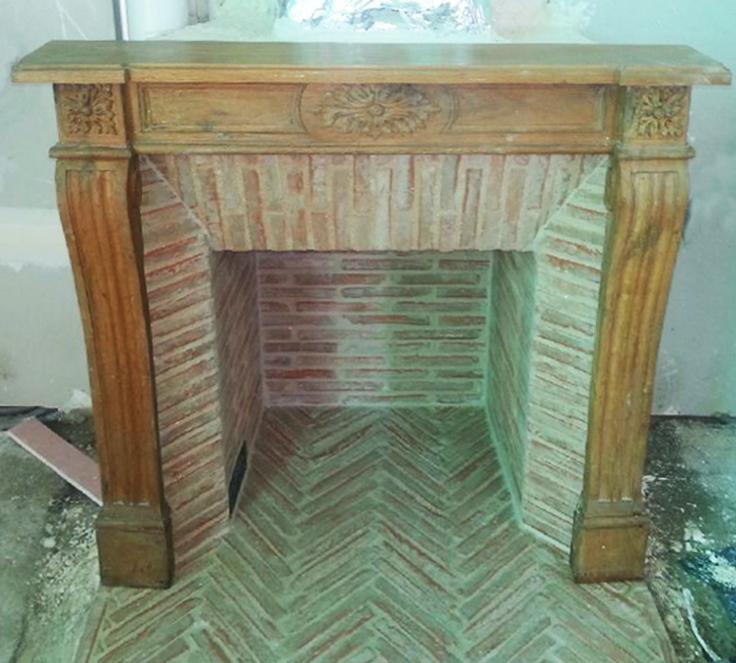 Installation d'une cheminée de style Louis XVI en bois avec intérieur en briquettes réfractaires