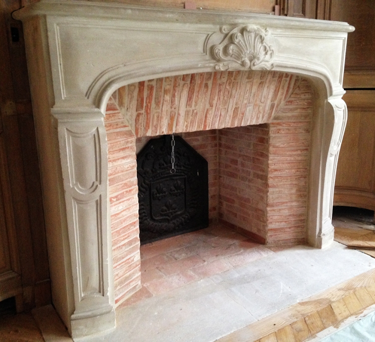 Pose d'une cheminée de style Régence en pierre avec intérieur en briquettes réfractaires.