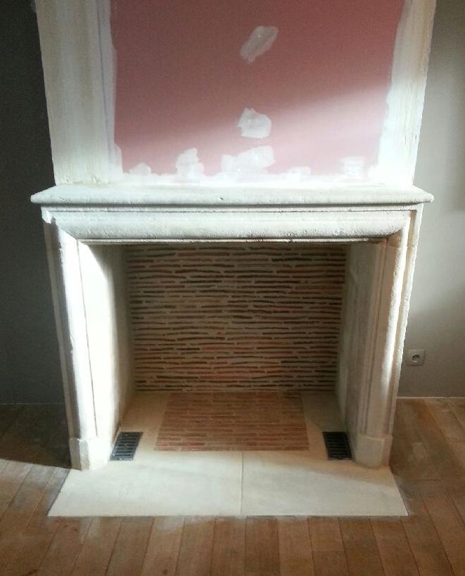 Une cheminée Louis XIV en pierre installée avec un intérieur réalisé en briquettes réfractaires.