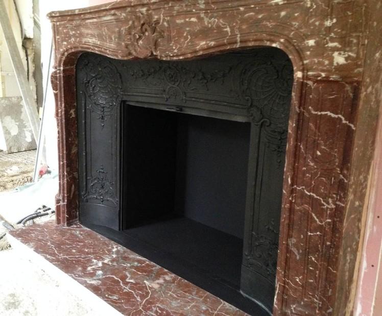 Une cheminée d'époque Louis XV en marbre avec son intérieur en fonte