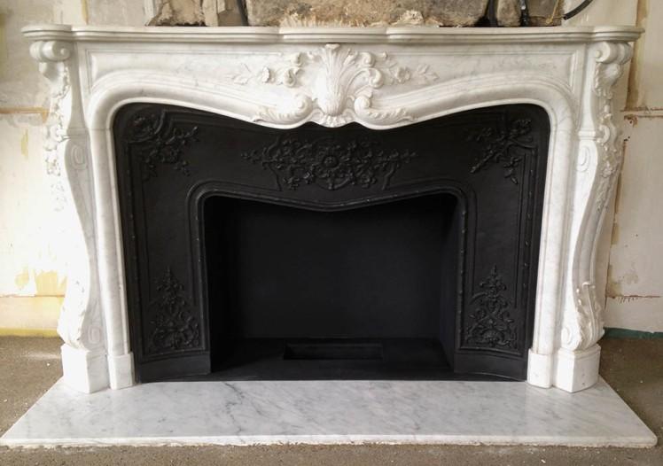 Une belle cheminée de style Louis XV en marbre avec intérieur en fonte. Le foyer est prêt à accueillir un brûleur à l'éthanol.