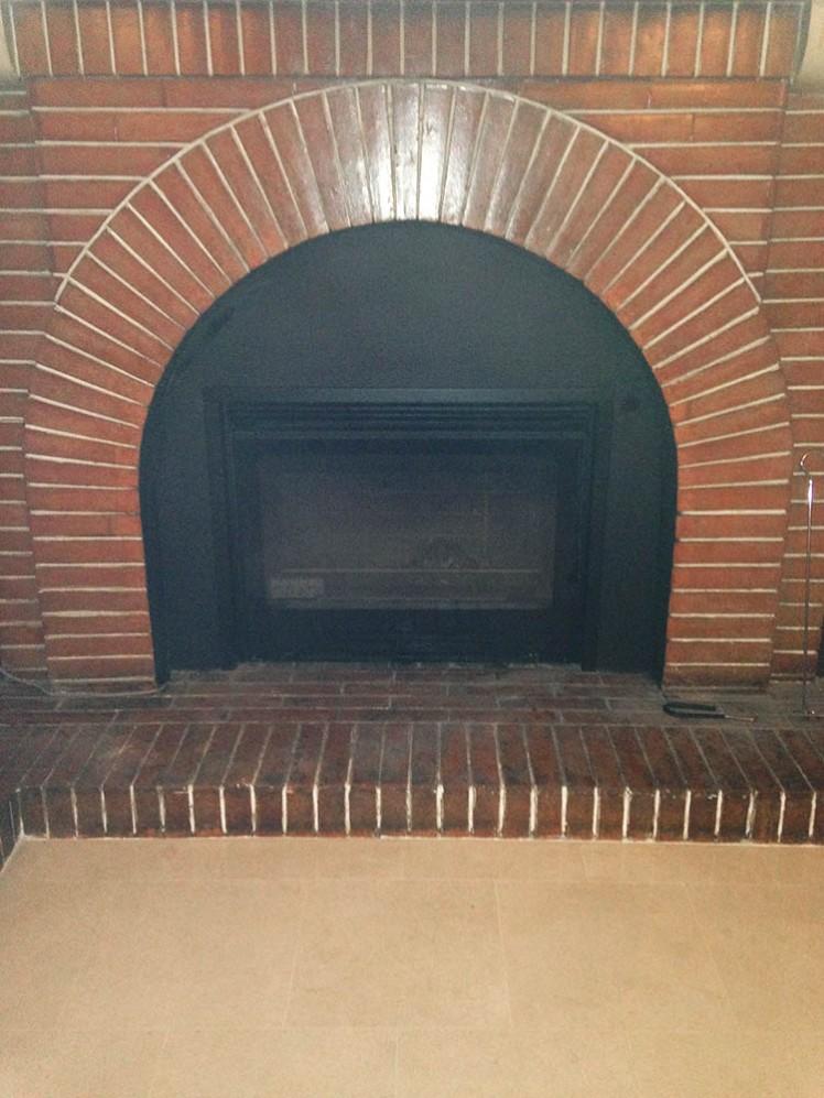 Un insert installé dans une cheminée existante.