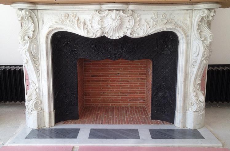 L'installation d'une exceptionnelle cheminée ancienne de style Louis XV en marbre de Carrare à Paris.