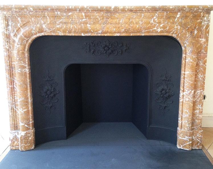 Pose d'une cheminée de style Louis XIV en marbre Rouge du Nord avec foyer en acier.