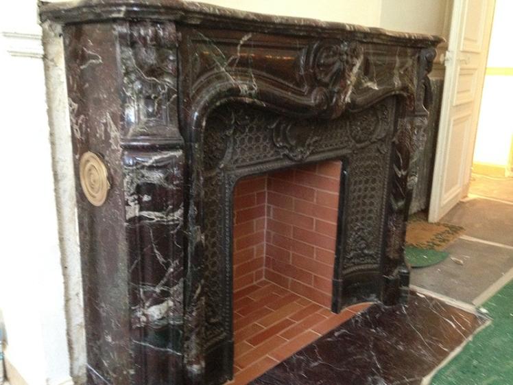 Installation d'une cheminée ancienne haussmannienne dans un beau marbre Rouge Levanto