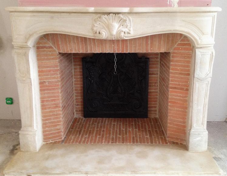 Une cheminée de style Louis XV en pierre avec un intérieur complet en briquettes réfractaires.