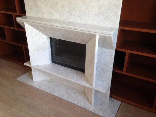 Une cheminée moderne en plaques de marbre blanc veiné avec insert installée.